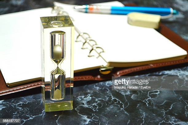 Hourglass And Books On Table