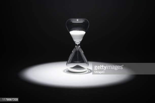 hourglass in the spotlight - prazo imagens e fotografias de stock