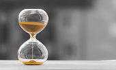 Hourglass on a black white blurred background. Time is money.