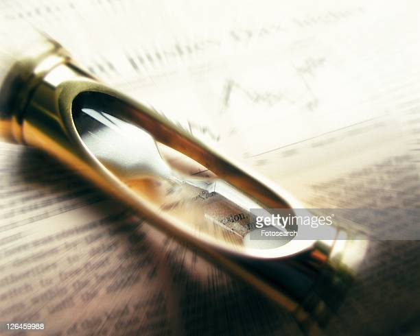 Hourglass on financial press, blurred motion, high angle view, close up