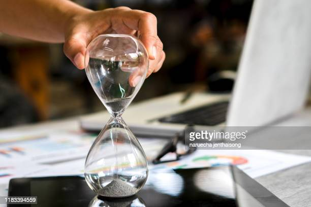 hourglass on laptop computer. concept for time management and countdown to deadline - countdown stock pictures, royalty-free photos & images