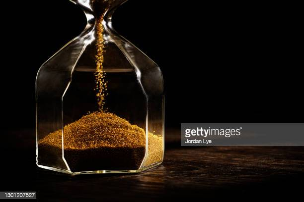 hourglass with golden sand - eternity stock pictures, royalty-free photos & images