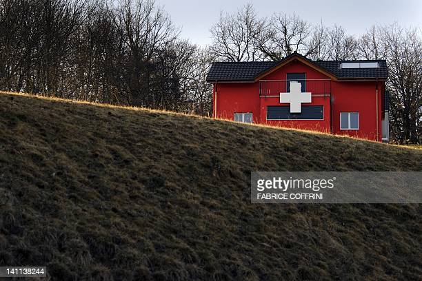 A house adorned with a white cross like the Swiss flag is seen on March 11 2012 in Moudon Swiss citizens accepted a referendum on Federal level to...