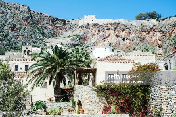 house against rocky mountain at monemvasia on sunny day - peloponnese stock photos and pictures