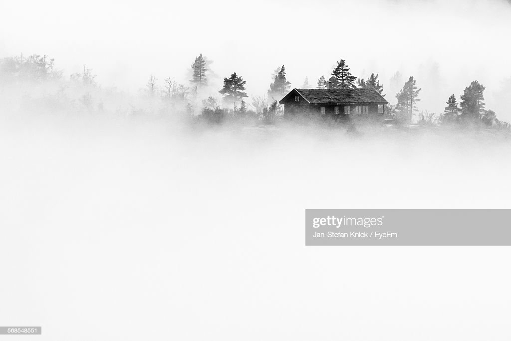 House Amidst Foggy Field : Stock Photo