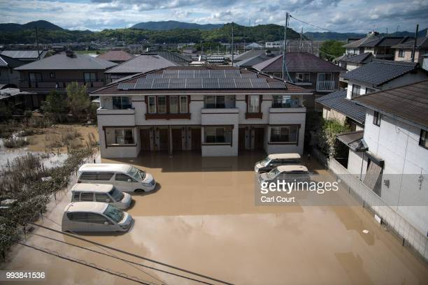 House and cars lie partially submerged in floodwater following days of torrential rain, on July 8, 2018 in Kurashiki near Okayama, Japan. Over 70...