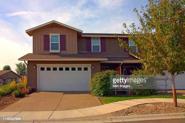 house and driveway in suburban neighborhood - american suburb neighborhood stock-fotos und bilder