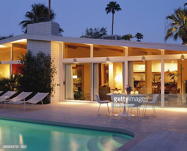 house and swimming pool lit at night - palm springs california stock pictures, royalty-free photos & images