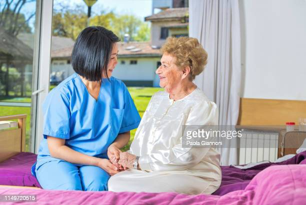 house assistance. asian caregiver smiling at senior lady. assisted living - gerontology stock pictures, royalty-free photos & images