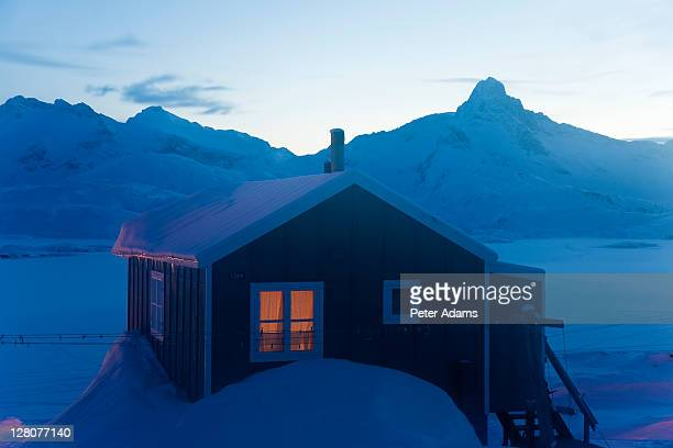 house at dusk, tasiilaq, e. greenland - peter adams stock pictures, royalty-free photos & images