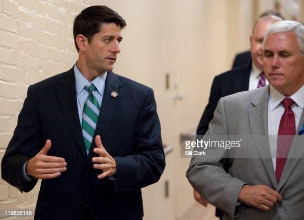 House Budget chairman Paul Ryan RWisc speaks with Rep Mike Pence RInd as they arrive for a meeting of the House Republican Conference in the basement...