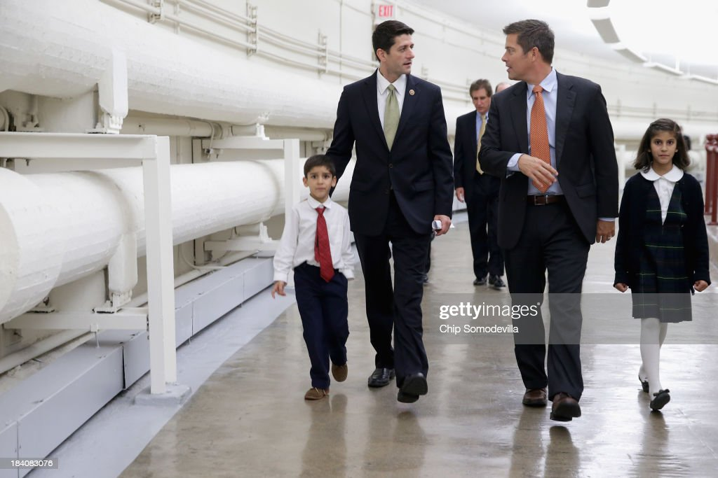 House Budget Committee Chairman Paul Ryan (R-WI) and Rep. Sean Duffy (R-WI) walk with Duffy's nephew and niece through the tunnel to the Longworth House Office Building October 11, 2013 in Washington, DC. Ryan published an op-ed Wednesday calling on his fellow Republicans and Democrats to negotiate not over Obamacare but about Òcommon-sense reforms of the countryÕs entitlement programs and tax code.Ó