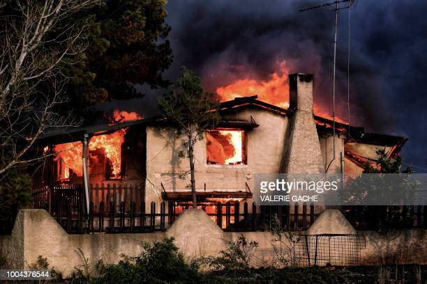 A house burns during a wildfire in Kineta near Athens on July 23 2018 More than 300 firefighters five aircraft and two helicopters have been...