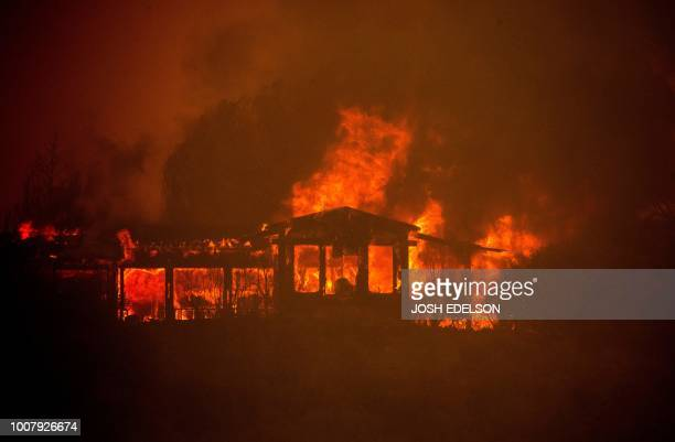 A house burns during the Mendocino Complex fire near Finley California on July 30 2018 Thousands of firefighters in California made some progress...