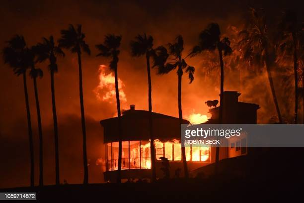 TOPSHOT A house burns during the Woolsey Fire on November 9 2018 in Malibu California About 75000 homes have been evacuated in Los Angeles and...