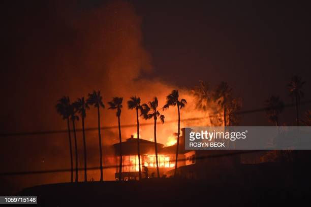 A house burns during the Woolsey Fire on November 9 2018 in Malibu California About 75000 homes have been evacuated in Los Angeles and Ventura...