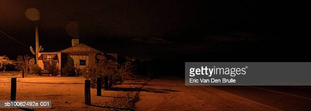 house by side of desert road, night - eric van den brulle stock pictures, royalty-free photos & images