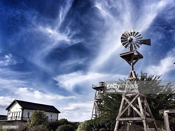 House By Traditional Windmill Against Sky