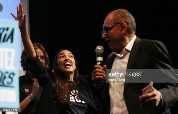 S House candidate Alexandria OcasioCortez L waves to supporters at a progressive fundraiser on August 2 2018 in Los Angeles California The rising...