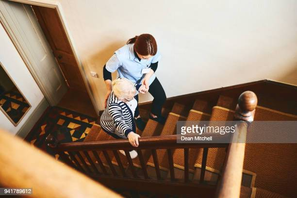 house caregiver helping senior woman to climb up the stairs - railings stock pictures, royalty-free photos & images