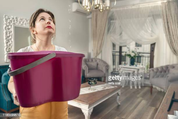 house ceiling is flowing - woman holding bucket while water droplets leak from ceiling - roof stock pictures, royalty-free photos & images