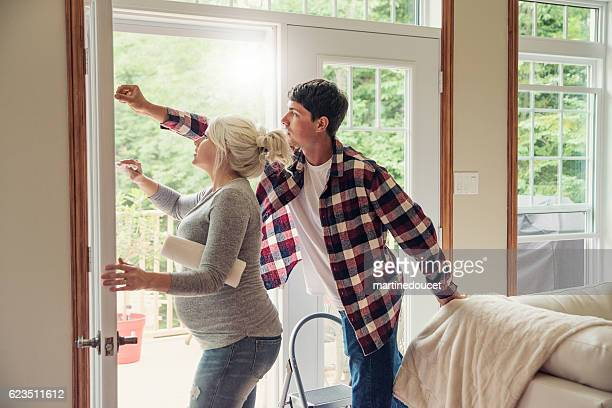 House chores time for young expecting couple, cleaning window.