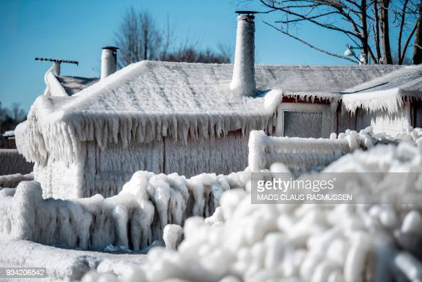 TOPSHOT A house completely covered by ice and icicles is pictured on the coast at Faxe Bay South of Copenhagenon March 19 as temperatures remain...