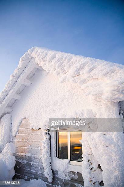 House covered in snow against a blue sky