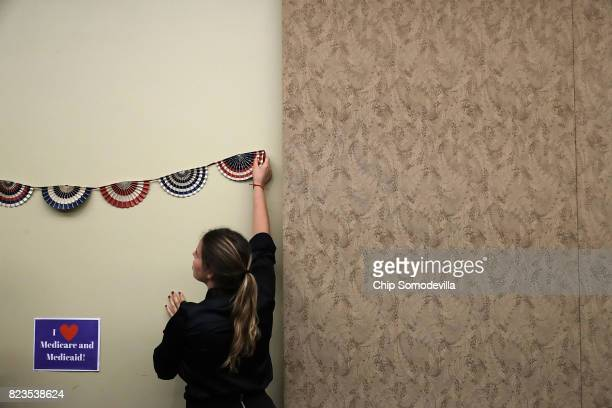 House Democratic caucus staff members prepare a background for photographs before an event to celebrate the 52nd anniversary of Medicaid and Medicare...