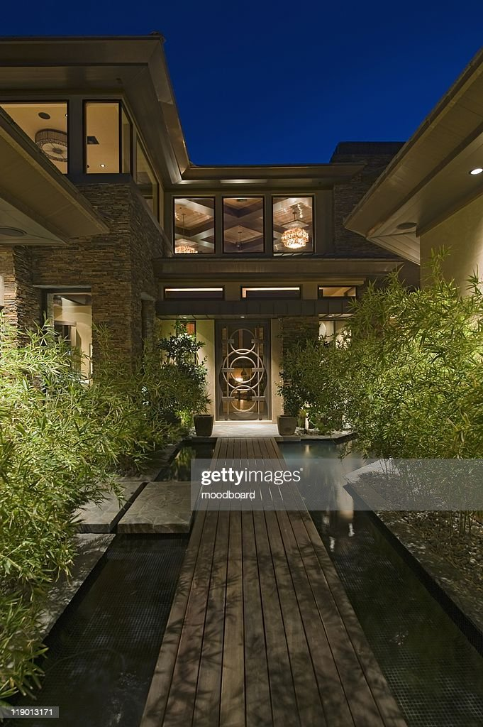 House Exterior At Night With Wooden Walkway Over Water : Stock Photo