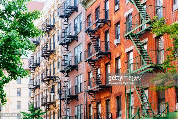 house facade with fire escape stairs in east village, manhattan, new york - apartment stock pictures, royalty-free photos & images