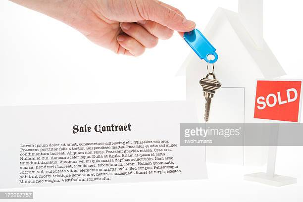 House figure with a SOLD sign a key and a sale contract