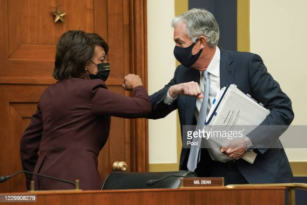 House Financial Services Committee Chairman Maxine Waters elbow bumps Federal Reserve Chairman Jerome Powell during a House Financial Services...