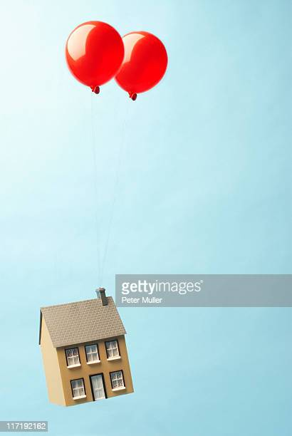 House floating away with two balloons
