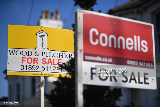 House For Sale signs are seen on a residential street in Tunbridge Wells, southeast England on March 1, 2021.