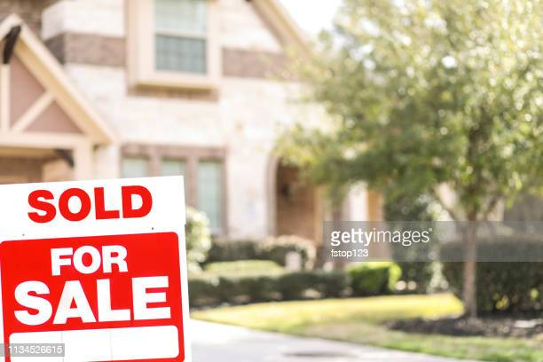 House for sale with real estate sign in yard.