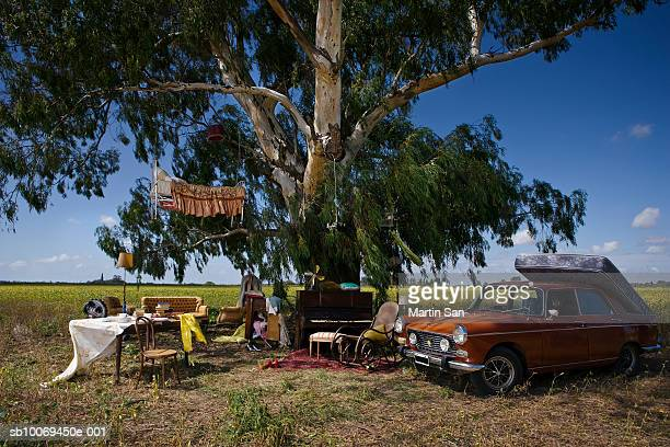 House furniture and car beneath tree in field