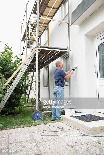 House garden man working DIY scaffolding