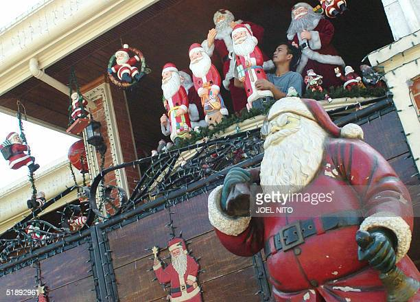 """House helper cleans a statue of Santa Claus in front of a house in a suburb of the Philippine capital 25 December 2004 that has been nicknamed """"the..."""