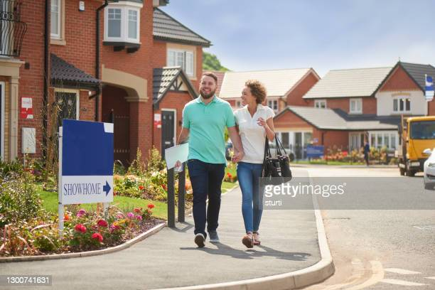 house hunting couple on housing development - mid adult couple stock pictures, royalty-free photos & images