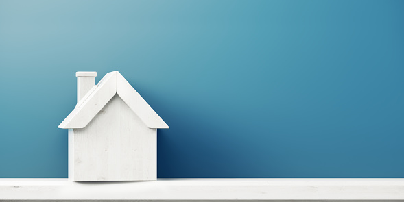 House Icon In Front Of Blue Wall - Real Estate Concept 1062626948