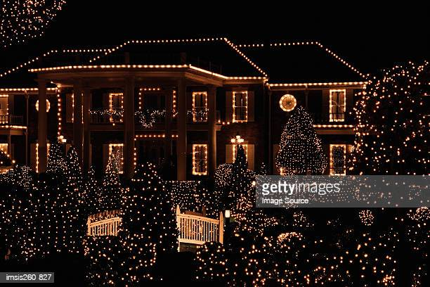 house illuminated by christmas lights - verlicht stockfoto's en -beelden