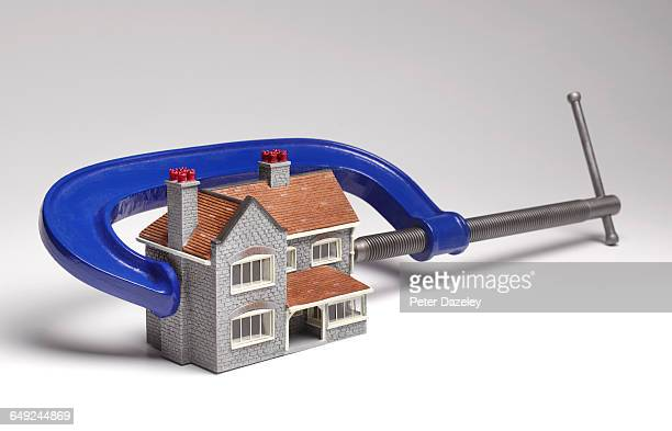 house in a financial clamp - trapped stock pictures, royalty-free photos & images