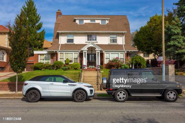house in bay ridge with mercedes-benz g-class suv and land rover range rover evoque suv parked in front of the house, and clear blue sky, brooklyn, new york, usa. - mercedes benz g class stock pictures, royalty-free photos & images