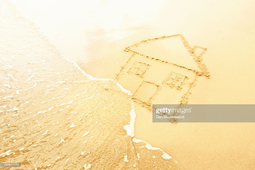 House in sand washed away by waves : Stock Photo