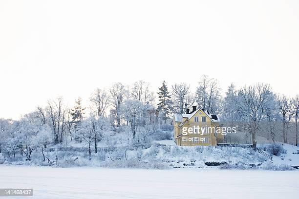 house in snowy landscape - stockholm stock-fotos und bilder