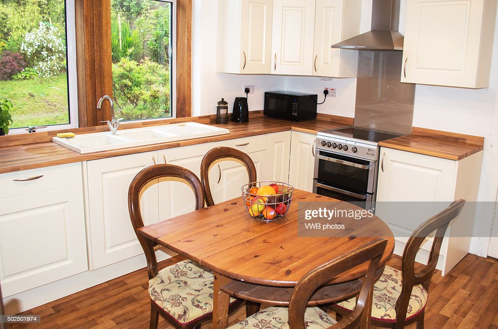 House Interior: Fitted kitchen with wood floor and central table : Stock Photo