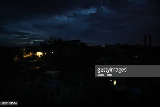 A house is lit by a generator in a neighborhood without grid power or running water about two weeks after Hurricane Maria swept through the island on...