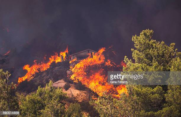 A house is surrounded by flames as the Bluecut Fire roars above Highway 138 on August 16 2016 in Phelan California