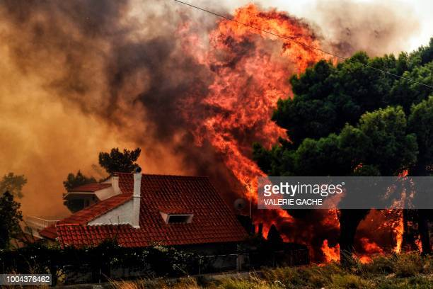 TOPSHOT A house is threatened by a huge blaze during a wildfire in Kineta near Athens on July 23 2018 More than 300 firefighters five aircraft and...